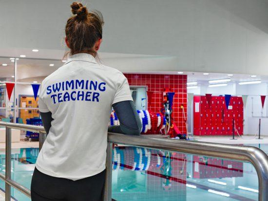 swimming teacher leaning on the side rails overlooking peel's main pool