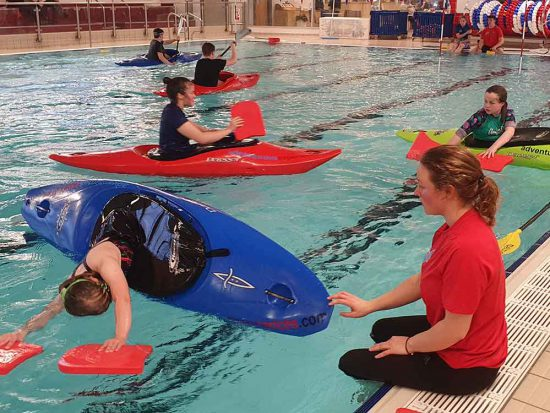 Instructor helping a kayaker in the main swimming pool