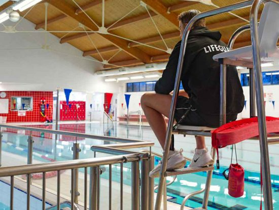 Lifeguard sitting high up overlooking the pools at Western Swimming Pool