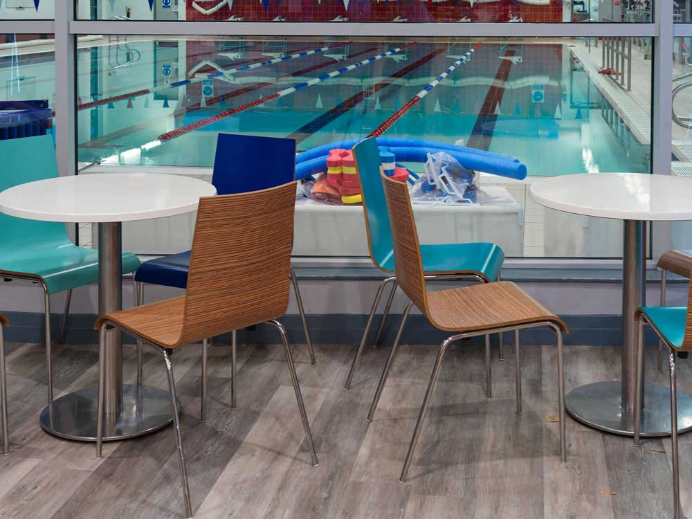 pair of tables with chairs in the cafe overlooking the main swimming pool in Peel